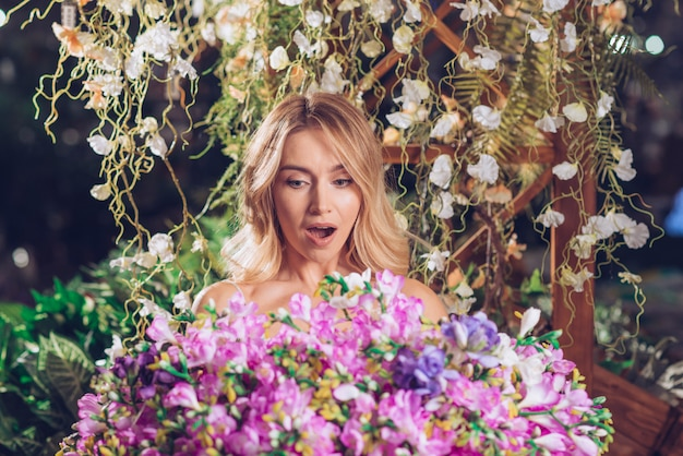 Blonde young woman looking at large flower bouquet surprisingly