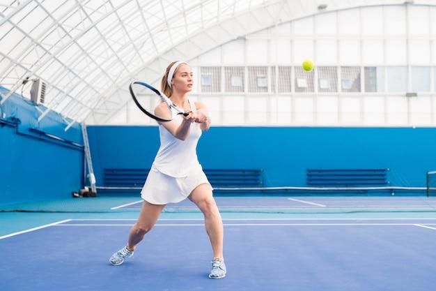 テニスをしている金髪の若い女性