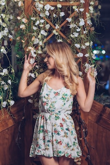Blonde young woman posing in front of flower decoration