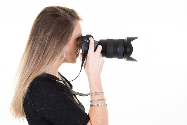Blonde young woman profile with professional digital slr camera on white