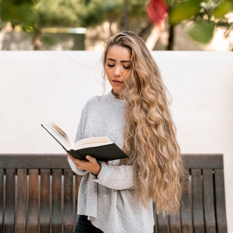 Blonde young woman reading a book outdoors