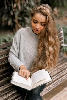 Blonde young woman reading a book outside