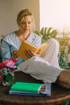 Blonde young woman reading book with vase on table