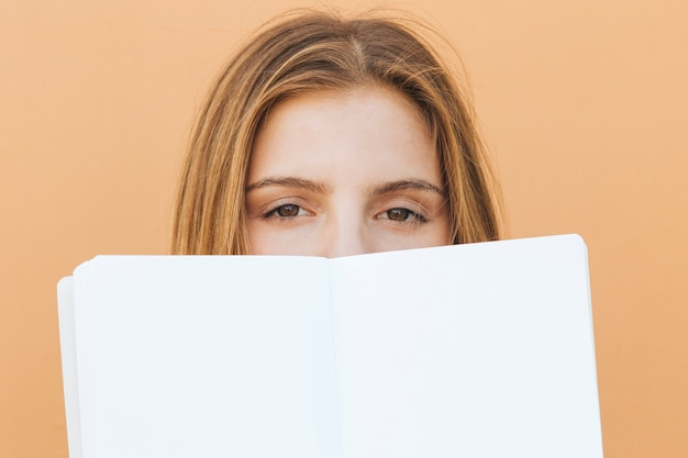 Blonde young woman's face with white book over her mouth