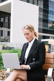 Blonde young woman sitting on bench using laptop