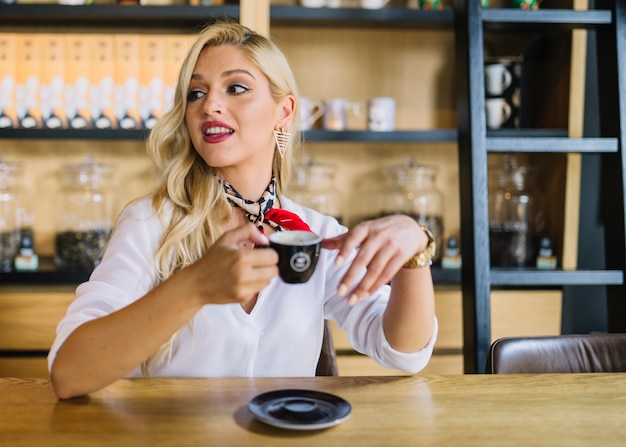 Blonde young woman sitting in the caf� holding coffee cup looking away