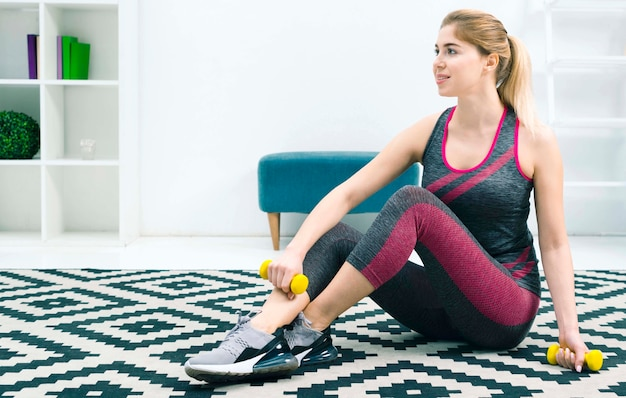 Blonde young woman sitting on carpet at home holding yellow dumbbells in hand
