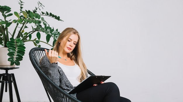 Blonde young woman sitting in chair writing notes on clipboard against white wall
