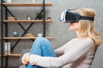 Blonde young woman sitting on sofa wearing virtual reality goggles