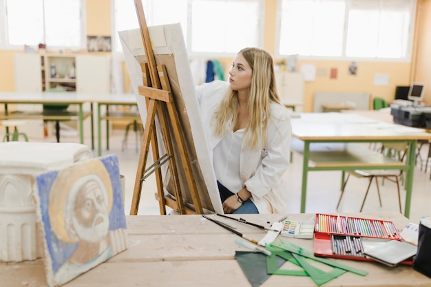 Blonde young woman sitting in workshop painting on easel