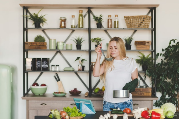 Blonde young woman smelling soup from the ladle in the kitchen