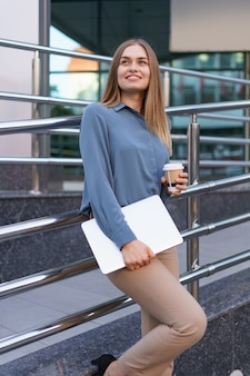 Blonde young woman smiling portrait holding laptop and coffee, wearing blue gentle shirt over modern building background