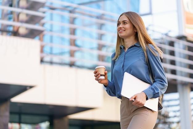 Ritratto sorridente della giovane donna bionda che tiene laptop e caffè, camicia delicata blu da portare sopra edificio moderno