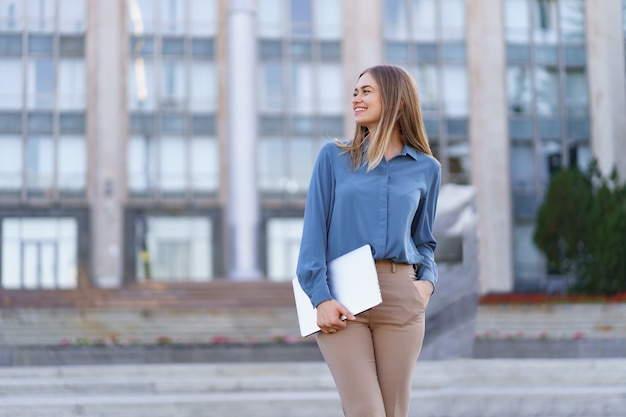 Ritratto sorridente della giovane donna bionda che indossa camicia delicata blu sopra la costruzione