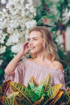 庭のクロトン植物の前に立っている金髪の若い女性