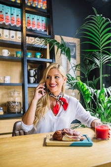 Blonde young woman talking on mobile phone having glass of juice and baked bread