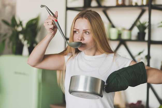 Blonde young woman tasting soup from the ladle