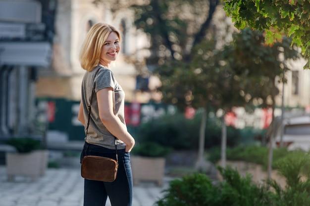 Белокурая молодая женщина гуляя и представляя на солнечной улице женщина гуляя в город на заходе солнца одна. образ жизни отдых отдыха выходные концепции