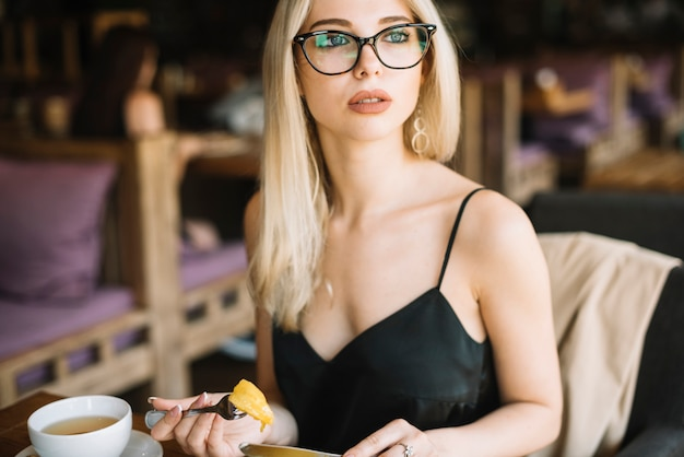 Blonde young woman wearing eyeglasses eating food in the caf���