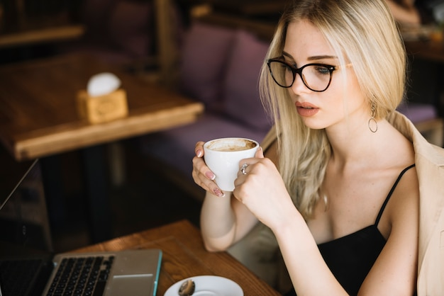 Blonde young woman wearing eyeglasses holding coffee cup in the caf���