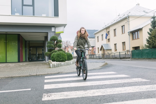 Blonde young woman wearing hooded top riding bicycle in the city