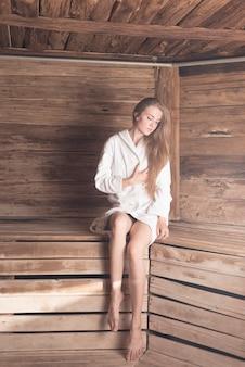 눈을 가진 금발의 젊은 여자 사우나에서 나무 벤치에 앉아 폐쇄