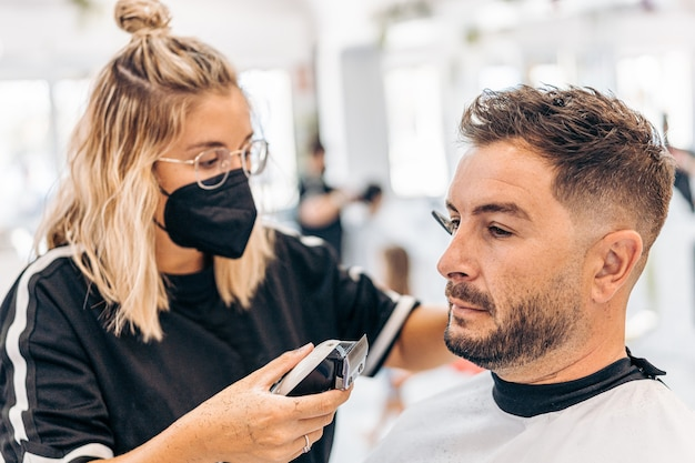 Blonde young woman with mask shaving a man with an electric machine in a barbershop