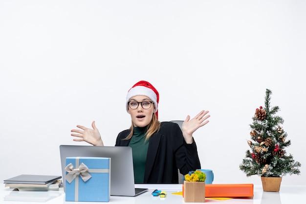 Giovane donna bionda con cappello di babbo natale e occhiali seduti a un tavolo con un albero di natale e un regalo su di esso su sfondo bianco