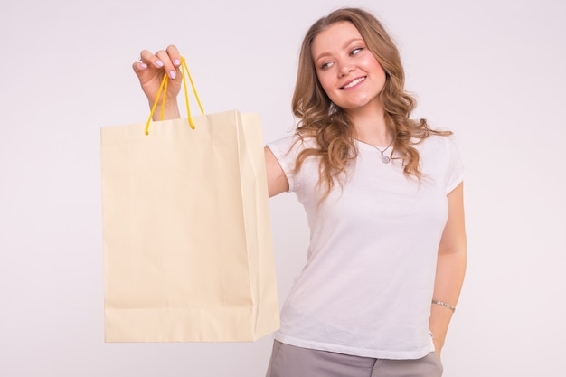 Blonde young woman with shopping bags on white surface
