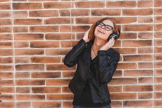 Blondhair cheerful woman enjoys music in big headphones