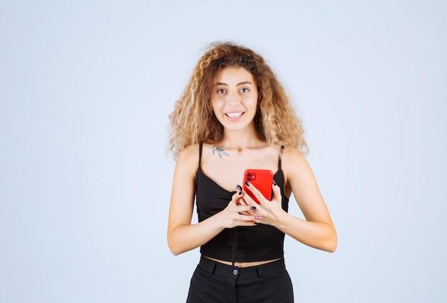 Блонди девушка разговаривает по телефону и чувствует себя позитивно.