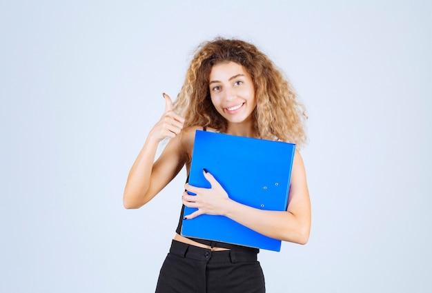 自信を持って青いフォルダーを保持している金髪の少女。