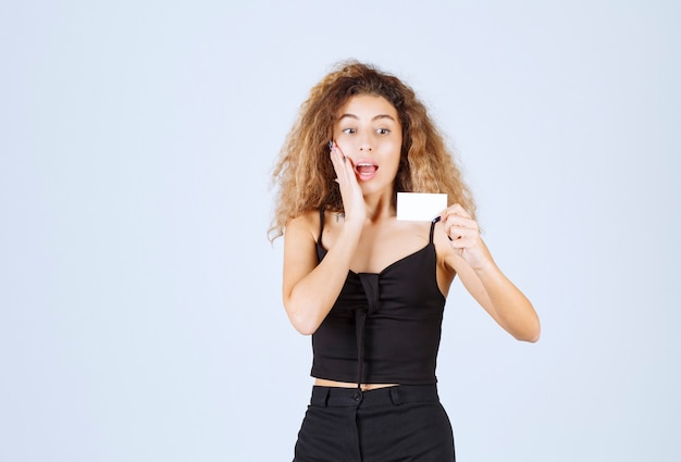 Блонди девушка держит визитную карточку и выглядит удивленным.