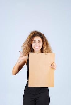 Блонди девушка держит картонную хозяйственную сумку и указывает куда-то еще.