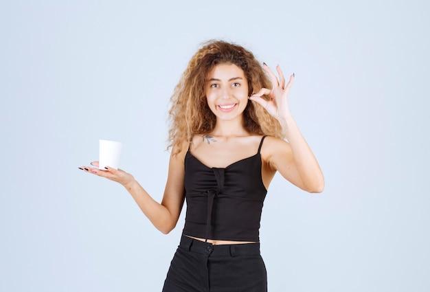 Блонди девушка держит чашку кофе и показывает, что ей нравится вкус.