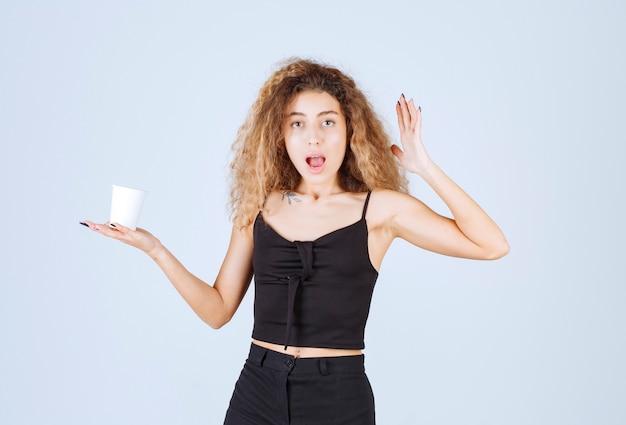 Блонди девушка держит чашку кофе и думает.