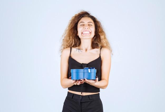 Ragazza bionda che tiene una confezione regalo blu e sembra sorpresa.