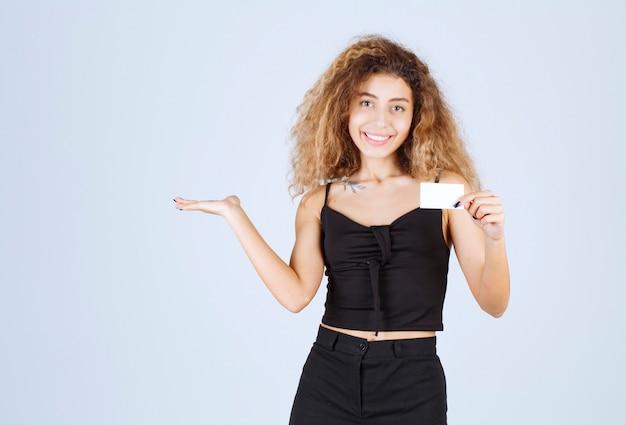 Ragazza bionda in possesso di un biglietto da visita e mostrando il suo collega.