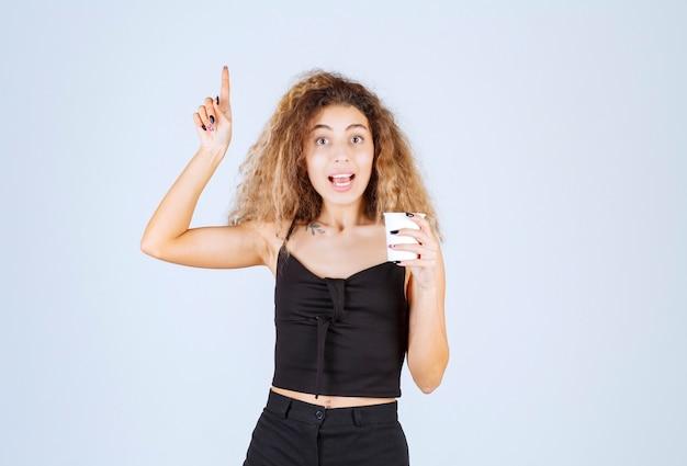 Ragazza bionda che tiene una tazza di caffè e che indica da qualche parte.