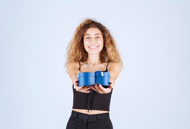 Блонди девушка предлагает или получает синюю подарочную коробку.