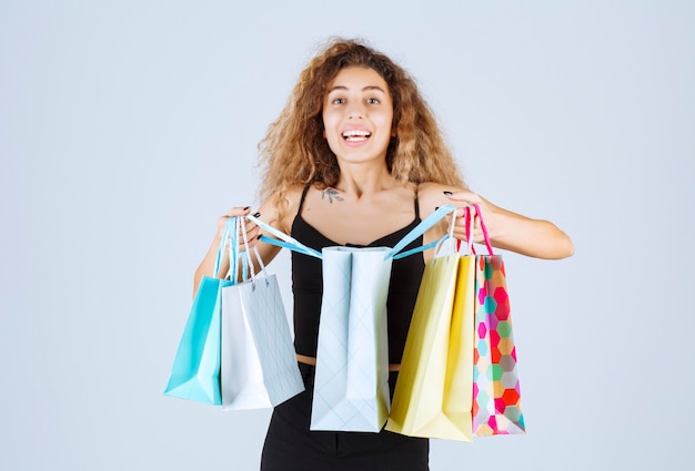 Blondie girl opening her colorful shopping bags and checking inside.