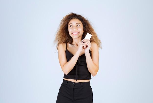 Блонди девушка с уверенностью представляет или получает визитную карточку.