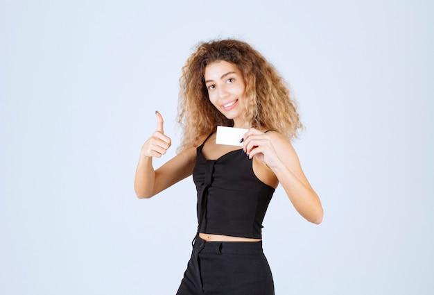 Ragazza bionda con un biglietto da visita che mostra il segno di godimento.