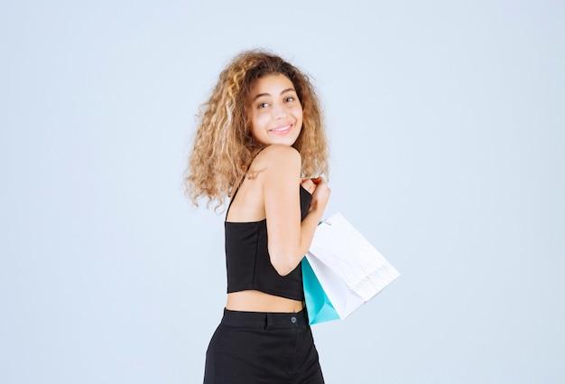 Блондинка с вьющимися волосами с удовлетворением держит свои красочные сумки для покупок.