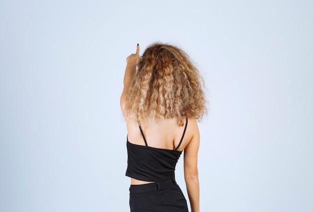 Блонди девушка с вьющимися волосами, указывающими зад.