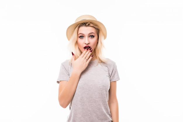 Blondie in hat covering teeth with hand isolated on white wall