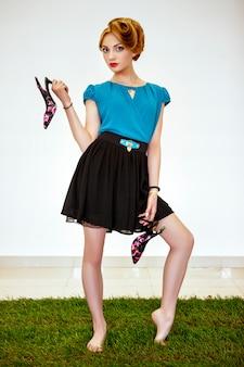 Блондиночка позирует на траве с туфлями