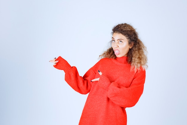Donna bionda in felpa rossa che punta da qualche parte sul lato sinistro.