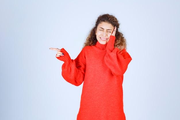 Donna bionda in felpa rossa che punta da qualche parte sul lato sinistro. Foto Gratuite
