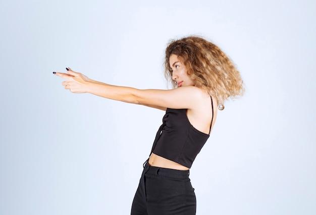 Блонди женщина показывает пистолет знак в руке.